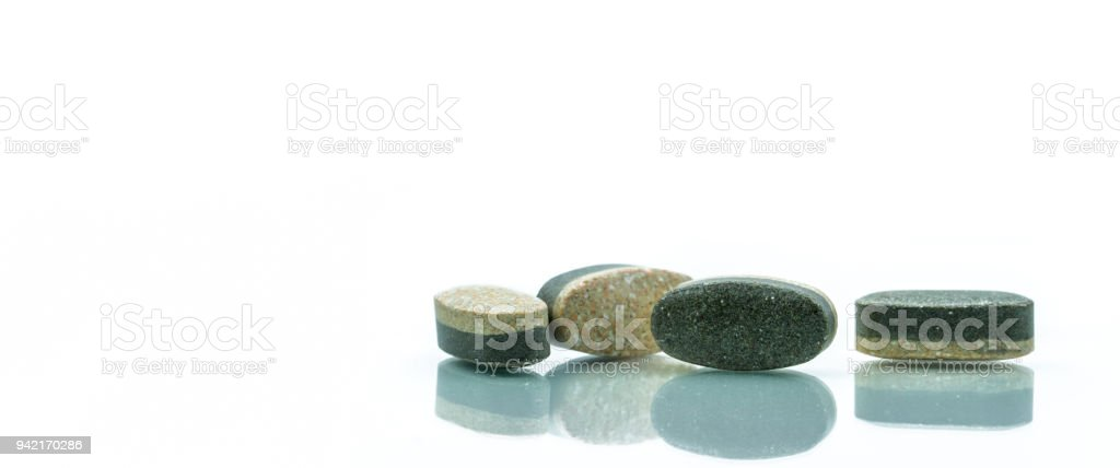 Essential Vitamins and minerals supplements dual layer tablet pills isolated on white background. Multivitamins plus reishi mushroom, wheatgrass, white tea and organic spirulina. Whole food nutrients. stock photo