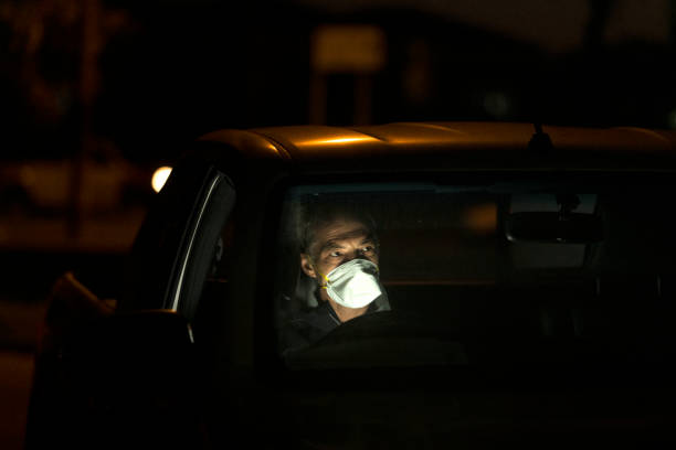 Essential worker driving at night wearing mask stock photo
