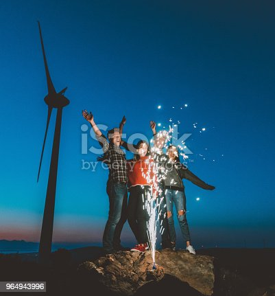 Portrait group of cool teen hipster friends dancing and celebrating with sparklers during partying and enjoy natural wind farm area at blue hour time outdoor. XXXL size taken with Canon 5D MIV
