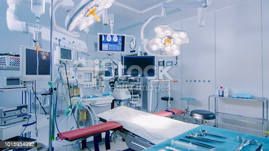 Establishing Shot of Technologically Advanced Operating Room with No People, Ready for Surgery. Real Modern Operating Theater With Working equipment,  Lights and Computers Ready for Surgeons and a Patients.