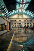 Train station in the Spanish metropole with passengers leaving and wet floor in autumn afternoon. It is the second biggest railway station in Barcelona.
