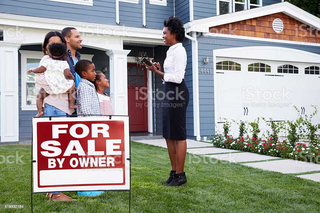 Estate agent and family outside house with a ' stock photo