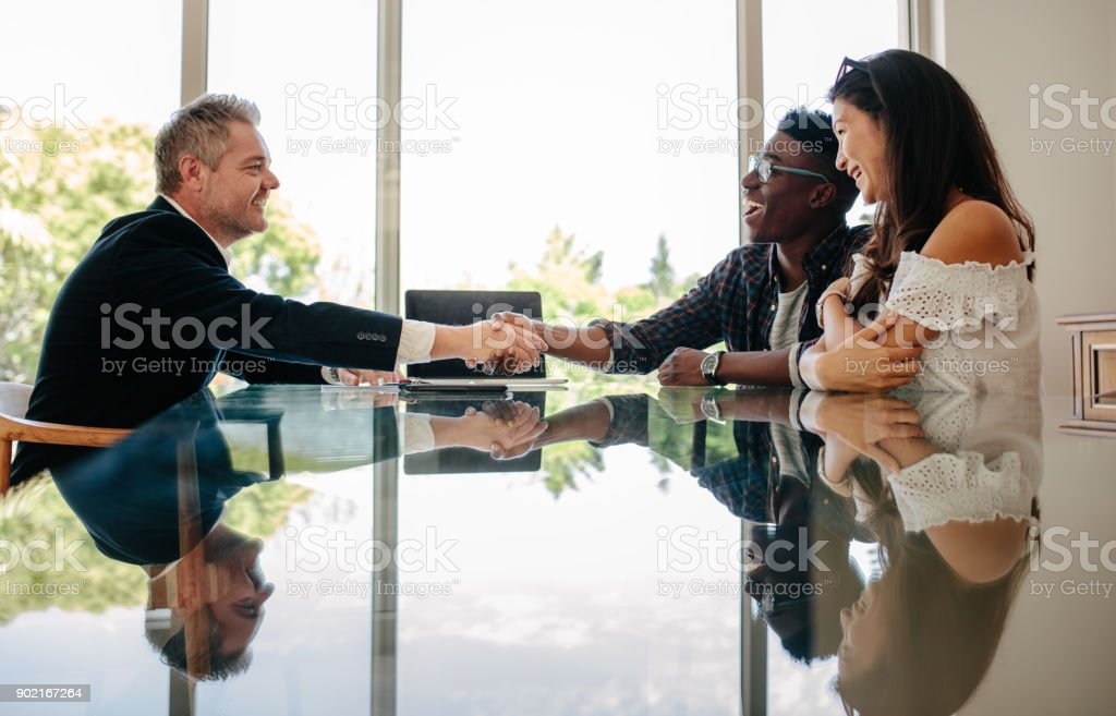 Estate agent congratulating couple after a property deal - foto stock
