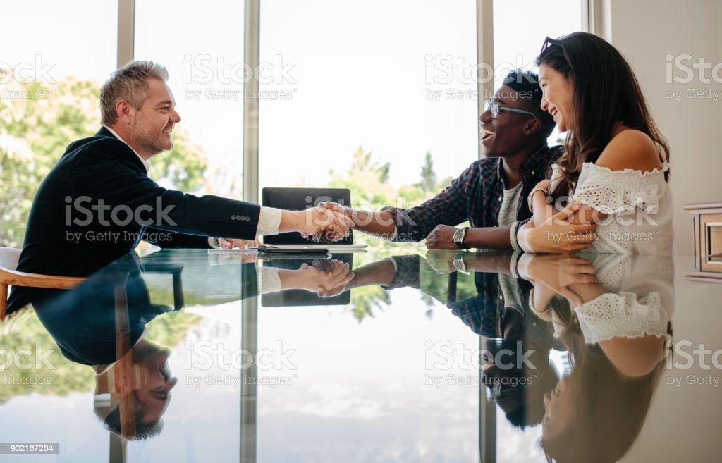 Felicitar a la pareja después de un acuerdo de propiedad inmobiliaria - foto de stock