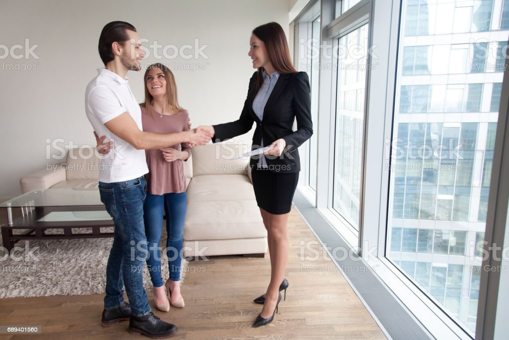 Estate agent congratulating young couple with property purchase, full length stock photo