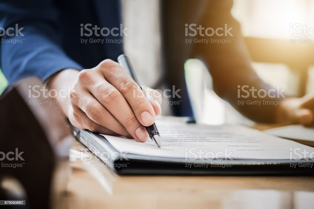 estate agent gives pen and documents agreement with customer to stock photo