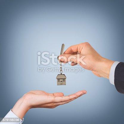 Estate agent giving house keys blue background