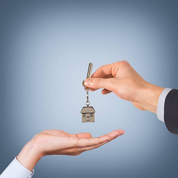 Estate agent giving house keys blue background stock photo