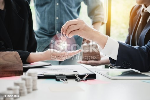 istock estate agent giving house keys  of customer  and holding dollar 911555464