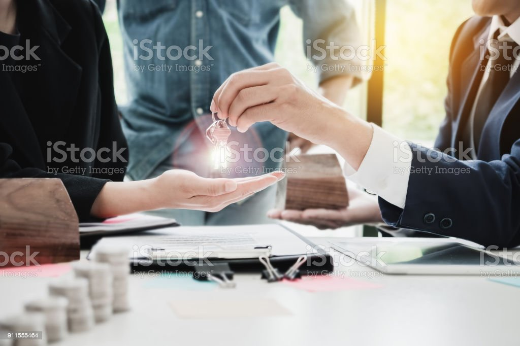 estate agent giving house keys  of customer  and holding dollar stock photo