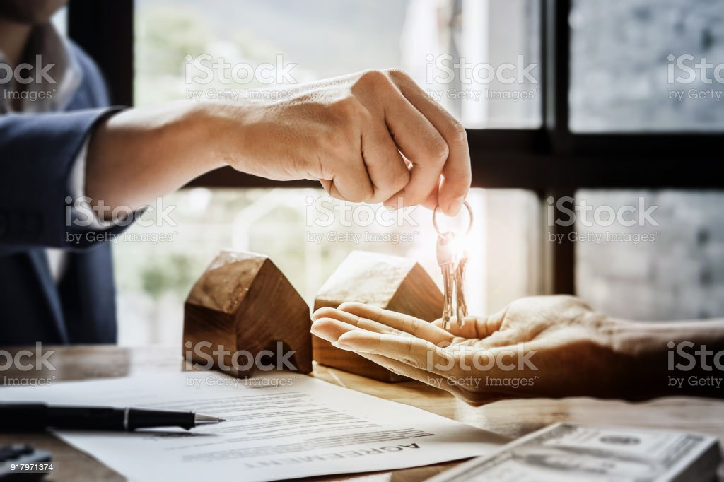 estate agent giving house keys  of customer  and holding dollar us bank at  agency office. agreement concept. stock photo