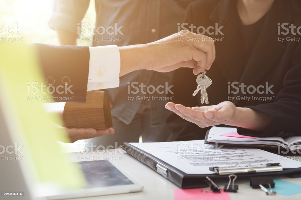 estate agent giving house keys to couple and sign agreement in office stock photo