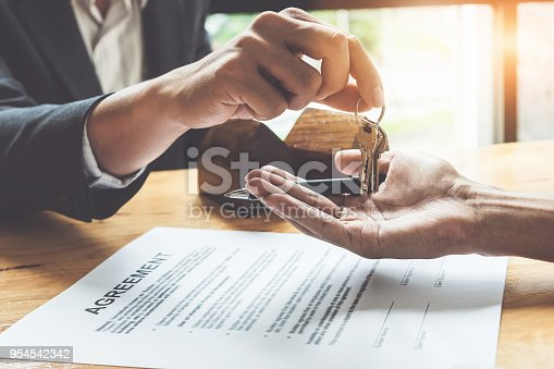 istock Estate agent giving house keys to customer and sign agreement in office. 954542342