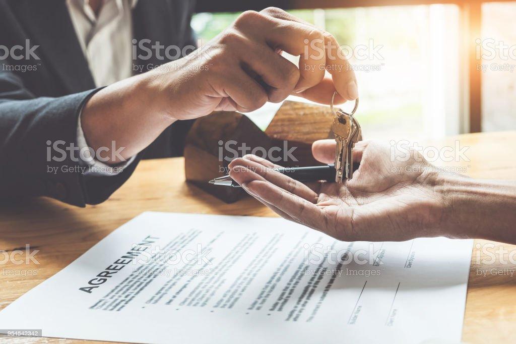 Inmobiliaria dando llaves al cliente y firman acuerdo en la oficina. - foto de stock