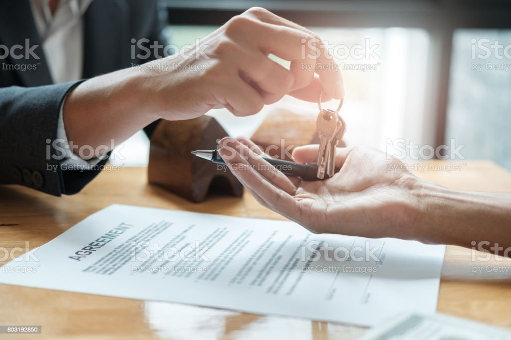 estate agent giving house keys to man and sign agreement in office - Royalty-free Adult Stock Photo