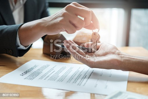 istock estate agent giving house keys to man and sign agreement in office 803192850