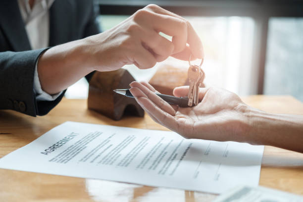 estate agent giving house keys to man and sign agreement in office stock photo