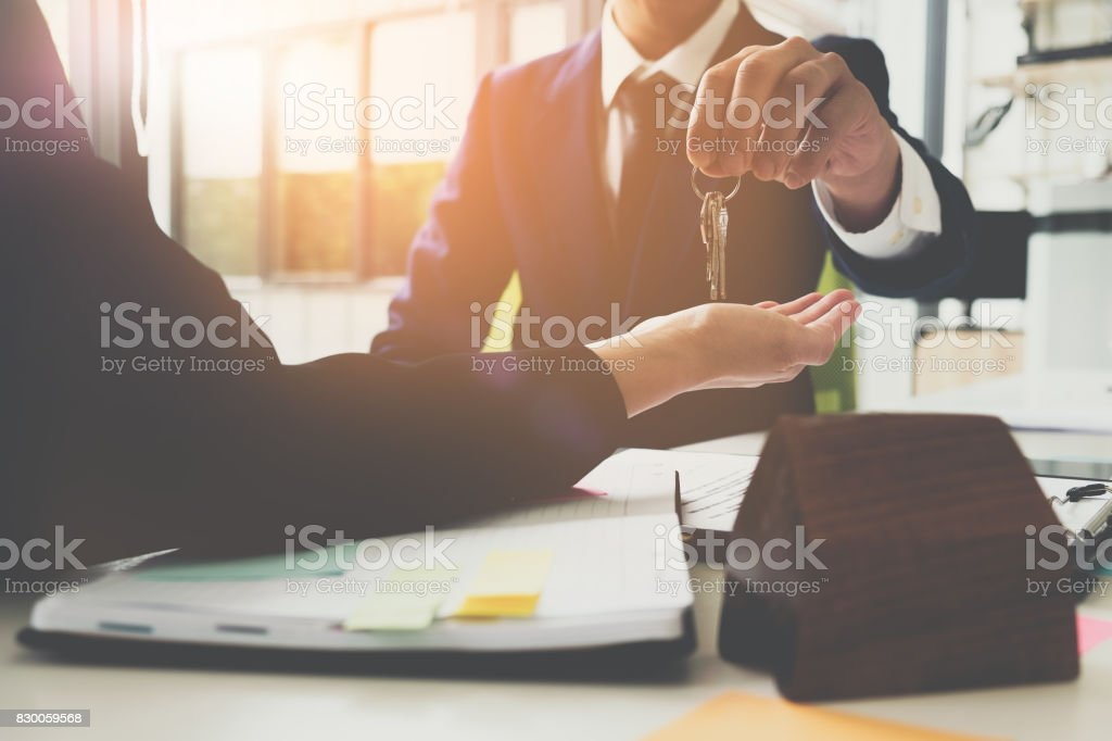 estate agent giving house keys to man and sign agreement in office royalty-free stock photo