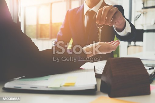 istock estate agent giving house keys to man and sign agreement in office 830059568