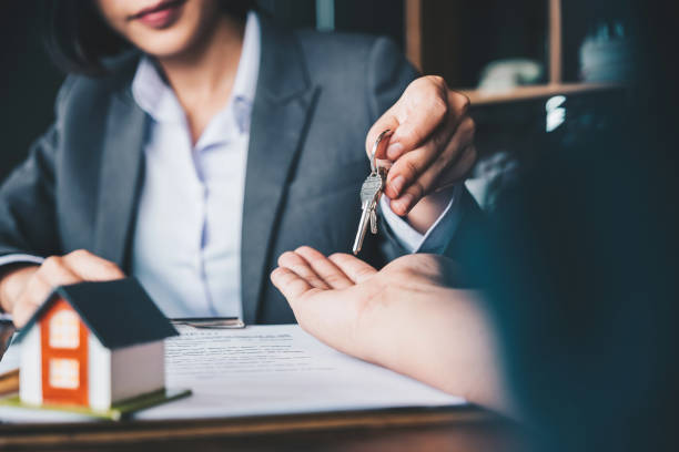 Immobilienmakler, der der Frau Hausschlüssel gibt und Vertrag im Amt unterschreibt – Foto