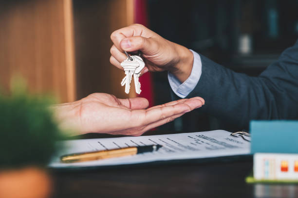 agente imobiliário que dá chaves da casa à mulher e assinam o acordo no escritório - chave - fotografias e filmes do acervo