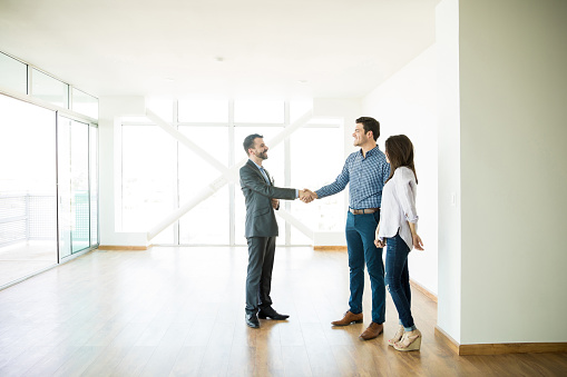 istock Estate Agent Greeting Couple During Visit To New Home 1023541030
