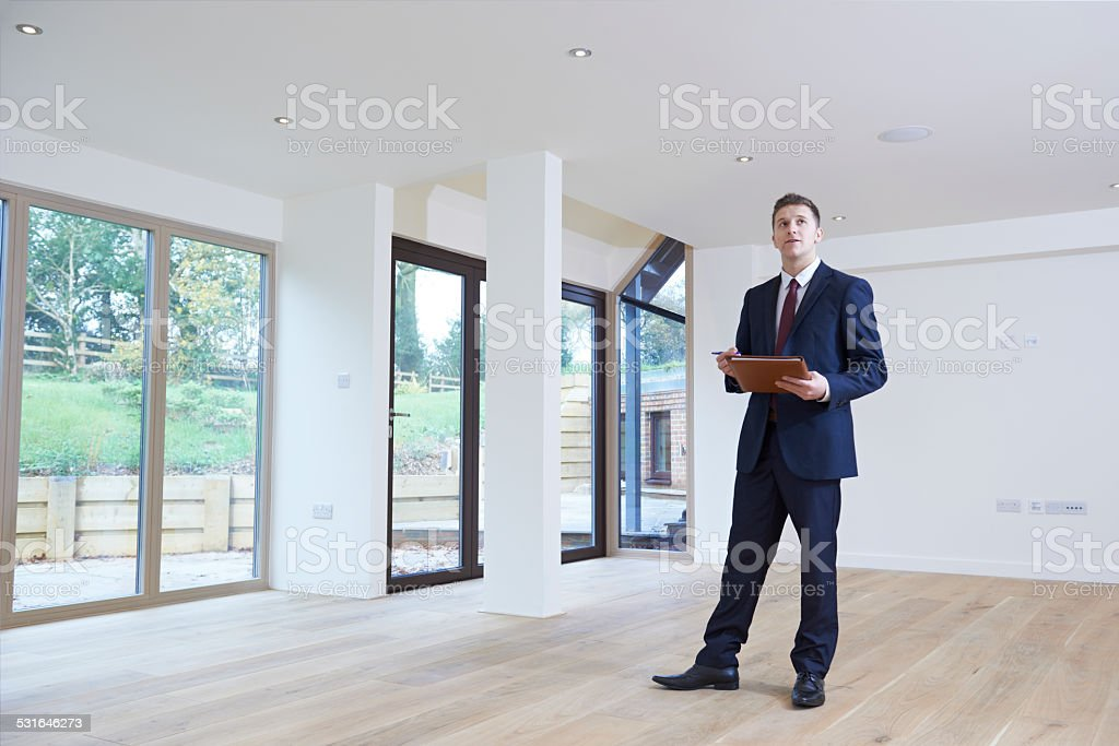 Estate Agent Looking Around Vacant Property For Valuation stock photo