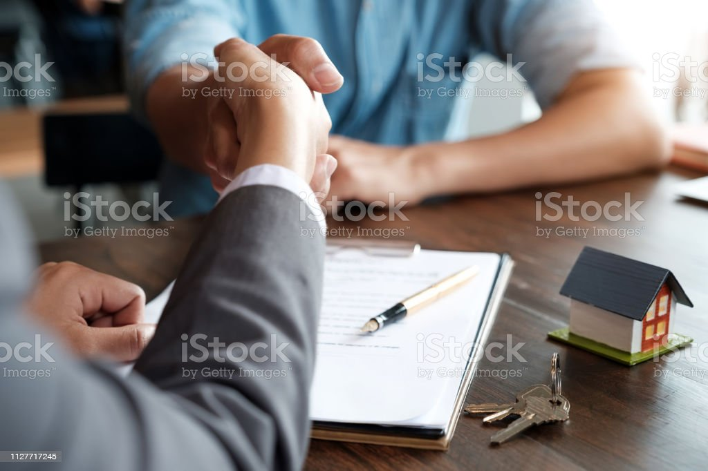 Estate agent shaking hands with his customer after contract signature Estate agent shaking hands with his customer after contract signature Adult Stock Photo