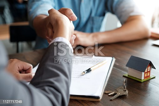 istock Estate agent shaking hands with his customer after contract signature 1127717245
