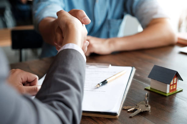 Estate agent shaking hands with his customer after contract signature Estate agent shaking hands with his customer after contract signature seller stock pictures, royalty-free photos & images