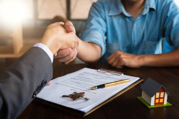 Immobilienmakler schüttelt mit seinem Kunden nach Vertragsunterzeichnung die Hände – Foto