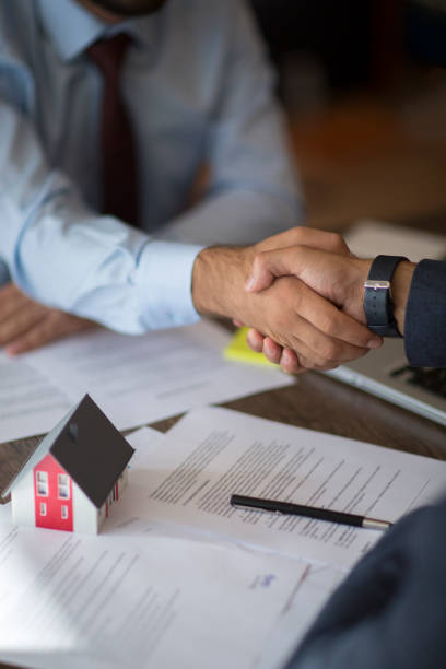 Estate agent shaking hands with his customer after contract signature stock photo