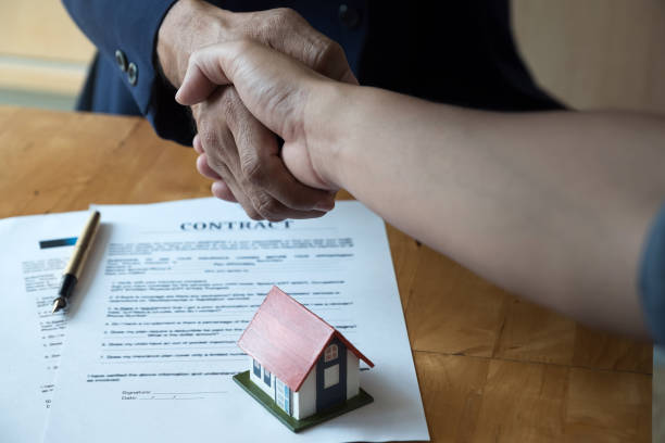 estate agent shaking hands with his customer after contract signature, contract document and house model on wooden desk - real estate law stock photos and pictures