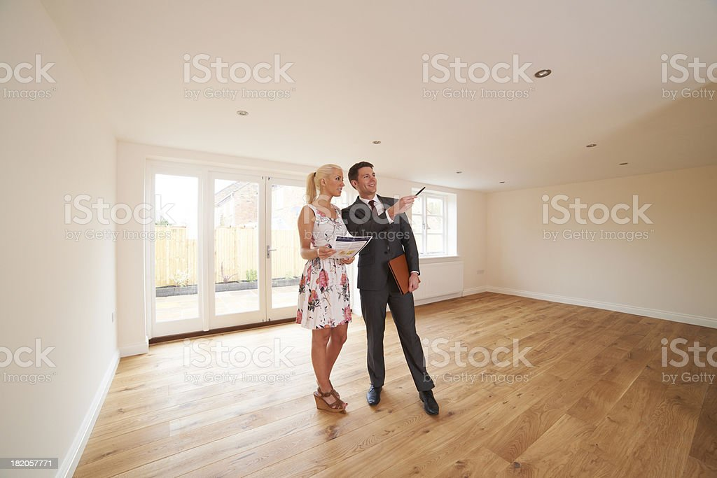 Estate Agent Showing Young Woman Around New Empty Property royalty-free stock photo