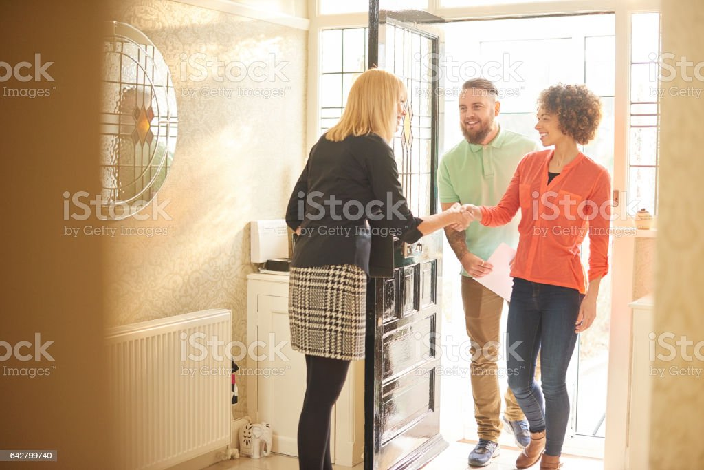 estate agent welcoming a couple to house viewing stock photo