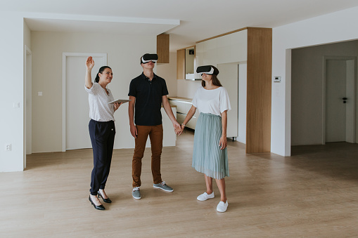 istock Estate agent with young couple wearing VR headsets in new apartment 1190395480