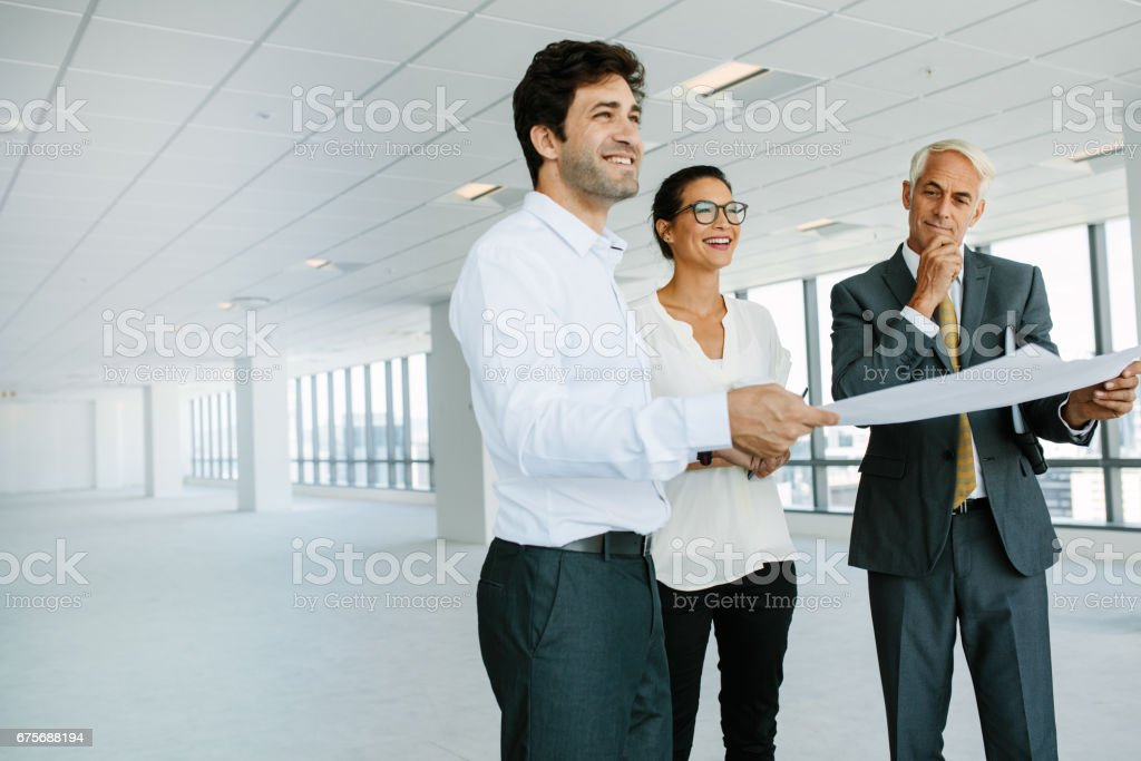 Estate broker and clients discussing over blueprint of new office space stock photo