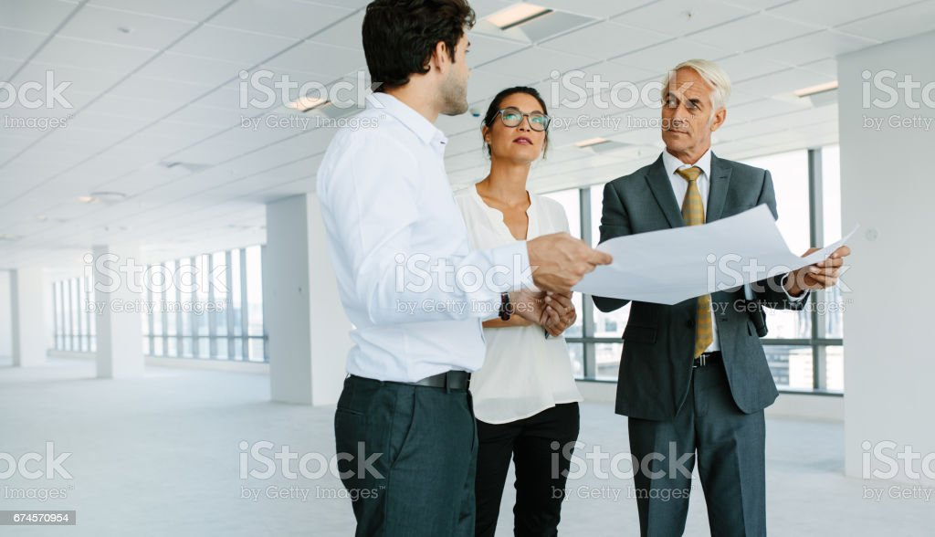Estate broker discussing blueprints of new office space with clients stock photo