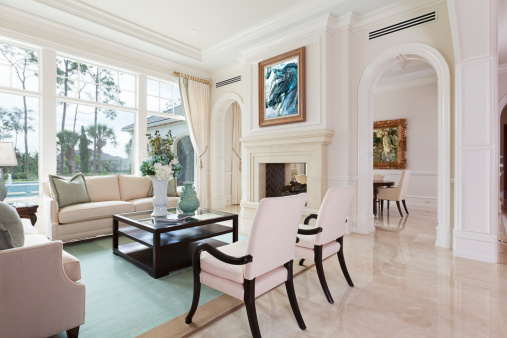 Beautiful living room overlooking a swimming pool at an estate home. (Paintings on walls are my images)