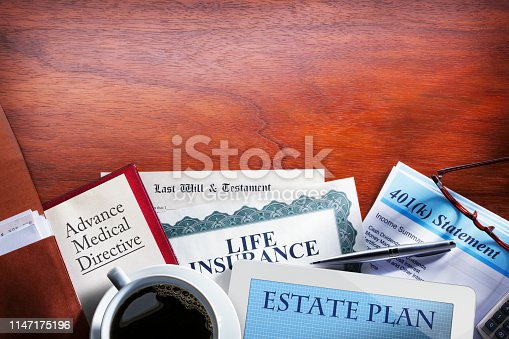 A desktop scene of various aspects relating to an estate plan are strewn about such as an advance medical directive, a last will and testament, life insurance documents, and a retirement plan statement.  A digital tablet and ballpoint pen rest next to a full cup of coffee.