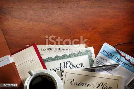 A desk scene with with many of the documents relating to estate planning. The scene includes a 401K statement, a life insurance policy, as well as a last will and testament.  A coffee cup, ball point pen and a pair of eyeglasses, and a datebook sit on top of all the documents.