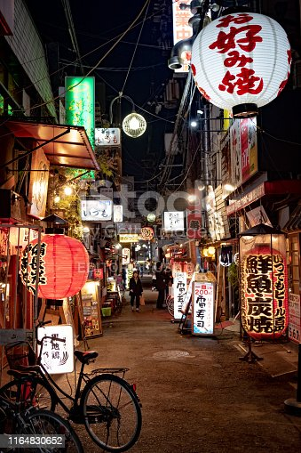 istock estaurants decorated with traditional old lanterns on back alley street in Namba, Japan. 1164830652