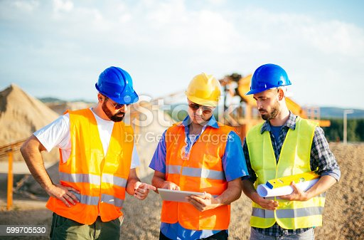 Engineers and architects on construction site, with blueprints and digital tablet. Three experts with hard hats on construction site. Image taken with Nikon D800 and developed from RAW in XXXL size. Location: Serbia, Central Europe, Europe