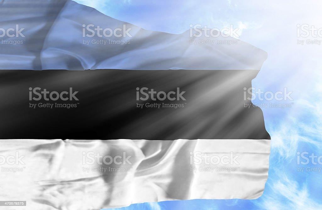 Estonia waving flag against blue sky with sunrays stock photo