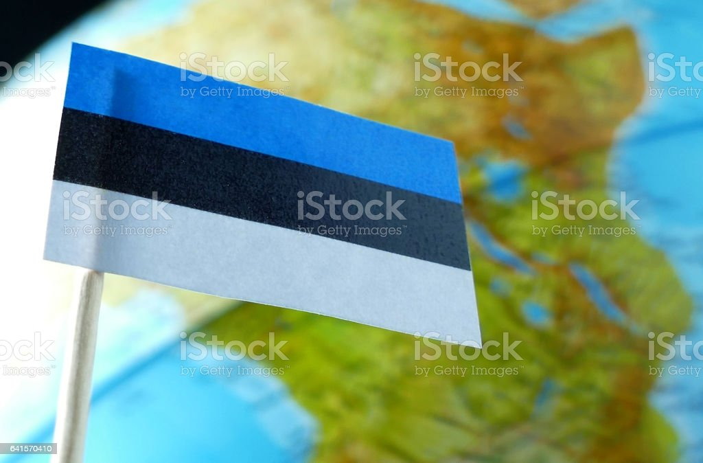 Estonian flag with a globe map as a background macro stock photo