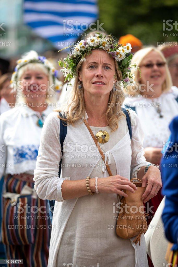 woman in traditional estonian clothing in streets of Tallinn, walking...