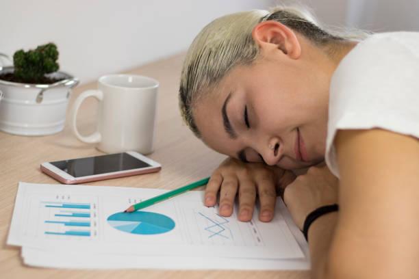 estudiante cansado de dormir en el escritorio con libros y móvil - estudiante stok fotoğraflar ve resimler