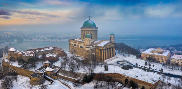 Esztergom, Hungary - Aerial panoramic view of the beautiful snowy Basilica of Esztergom with Slovakia at the background on a foggy winter morning stock photo
