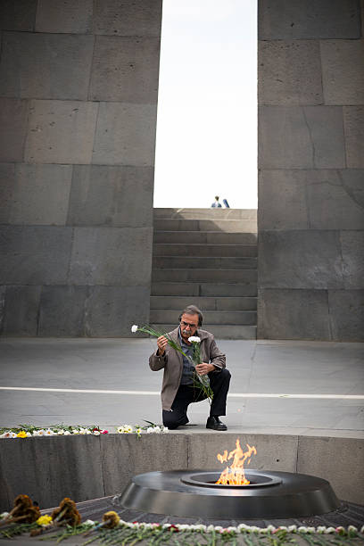 Eternal flame at the Armenian Genocide Memorial in Yerevan Yerevan, Armenia - October 4, 2016: A man lays flowers at the eternal flame at the Armenian Genocide Memorial in Yerevan, Armenia. armenian genocide stock pictures, royalty-free photos & images