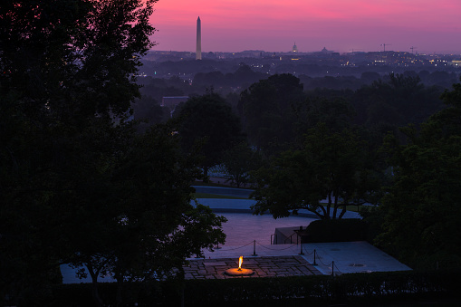 The sky over the Washington, D.C. skyline shows shades of pink and purple prior to sunrise from the John F. Kennedy eternal flame and presidential memorial in Arlington National Cemetery
